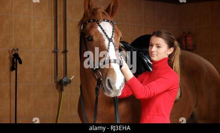 Schöne Mädchen mit ihrem Pferd im Stall. - Stockfoto