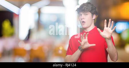 Jungen gutaussehenden Mann tragen rote T-Shirt über isolierte Hintergrund Angst und Furcht Ausdruck stop Geste mit den Händen entsetzt, geschockt zu schreien. - Stockfoto