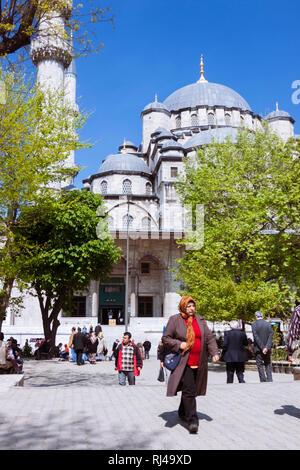 Istanbul, Türkei: Menschen gehen vorbei an der Neuen Moschee (Yeni Camii) zwischen 1660 und 1665 gebaut, ein Ottoman Imperial Moschee im Viertel Eminönü, auf der - Stockfoto