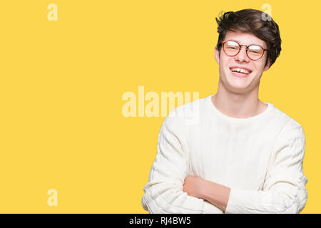 Jungen gutaussehenden Mann Brille über isolierte Hintergrund glücklich lächelnd mit verschränkten Armen in die Kamera schaut. Positive Person. - Stockfoto