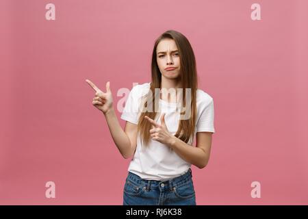 Nahaufnahme der ernsten strengen junge Frau trägt weiße Hemd sieht betonte und zeigte mit dem Finger über rosa Hintergrund isoliert - Stockfoto