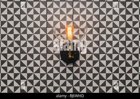 Transparenter Kristall runder Kronleuchter, wandleuchte Lampe mit Edison die Glühbirne an der Wand mit kleinen, dreieckigen Grafik schwarzen und weißen Fliesen. Konzept interior Loft, - Stockfoto