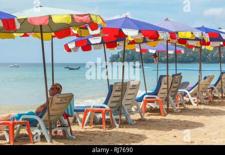 Reihe von Liegestühlen und bunten Sonnenschirmen und Liegestühlen auf der sandigen Küste am Surin Strand, an der Westküste von Phuket, Thailand - Stockfoto