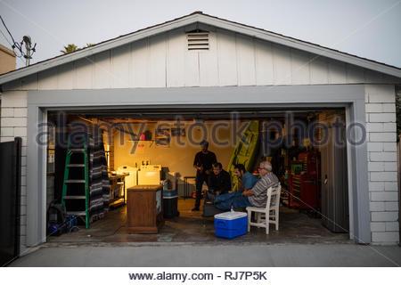 Latinx Männer Sport im Fernsehen in einer Garage. - Stockfoto