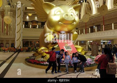 Touristen posieren vor einem riesigen GoldenPig mit Flügeln für chinesische Neujahrsfest in der Galaxie Hotel und Casino in Macau - Stockfoto