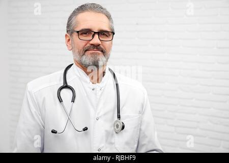 Professionelle HNO-Arzt auf Kamera und posiert im Studio mit weißem Hintergrund. Reife bärtige Arzt tragen in Weiß medizinische einheitliche und Gläser, mit Stethoskop um den Hals. - Stockfoto