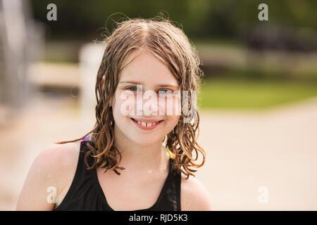Ein 10-jähriges Mädchen im Badeanzug mit nassen Haaren Lächeln am Pool im Sommer. - Stockfoto