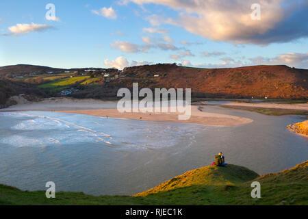 Zwei junge Frauen genießen Sie die Aussicht bei Three Cliffs Bay, Gower, Swansea, Wales, Februar. - Stockfoto