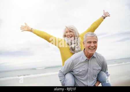Moderne pulsierende senior Paar huckepack Reiten am Strand - Stockfoto