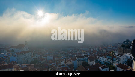 Antenne; nebligen Morgen im antiken Viertel Alfama der portugiesischen Hauptstadt; drone Blick auf hübsche kleine Häuser, Sonne über den Wolken steigend; Nat - Stockfoto