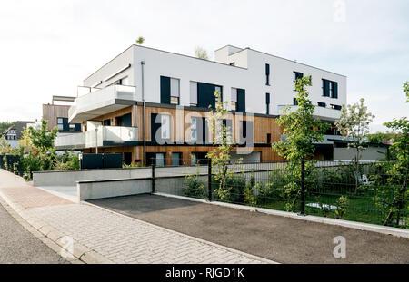 Moderne Stadthäuser in einem Wohngebiet mit mehreren neuen Wohnungen Gebäude durch grüne Außenanlagen im Zentrum Ruhige Nachbarschaft umgeben - Stockfoto