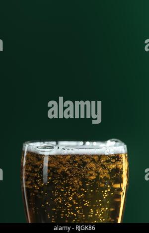 Nahaufnahme der Bier Glas mit Schaum und Blasen auf Grün, St Patrick's day Konzept isoliert - Stockfoto