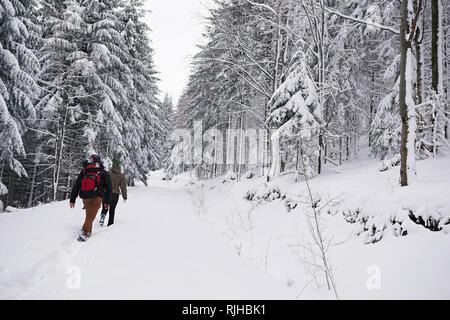 Paar wandern auf einem verschneiten Wald im Winter - Stockfoto