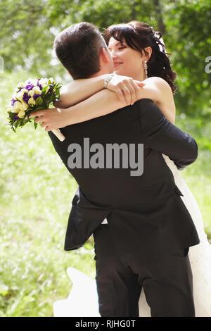 Die Braut und der Bräutigam am Hochzeitstag spinning für einen Spaziergang