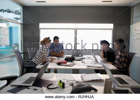 Tausendjährige Unternehmern an Laptops in Konferenzraum Sitzung arbeiten - Stockfoto