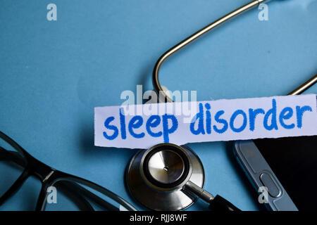 Konzeptionelle Bild mit Schlafstörungen Inschrift mit der Ansicht von Stethoskop, Brillen und Smartphone auf dem blauen Hintergrund. Medizinische konzeptionell. - Stockfoto