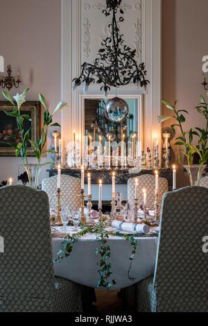 Quecksilber Kerzenständer auf Kaminsims und Tabelle mit Lilien unter dekorative Kronleuchter aus Kupfer aus dem späten 19. Jahrhundert. - Stockfoto