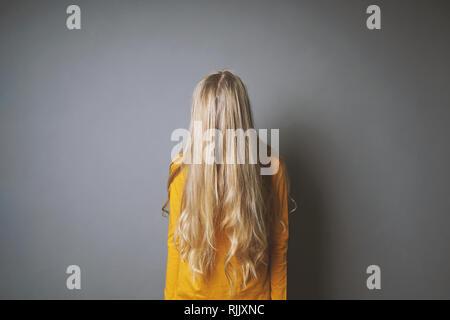 Deprimiert junge Frau ihr Gesicht verstecken hinter lange blonde Haare, schüchtern oder gleichgültig Jugendmädchen - Stockfoto