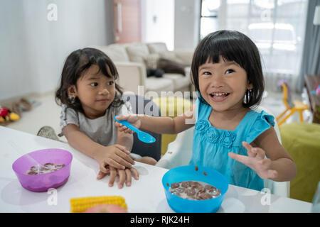 Kleine asiatische Mädchen zusammen zu frühstücken, - Stockfoto
