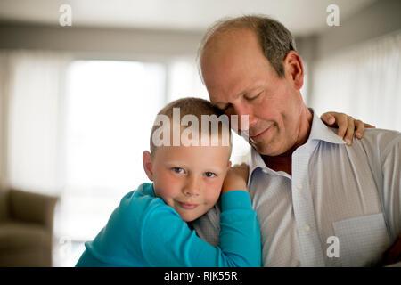 Portrait eines glücklichen jungen Jungen mit seine Arme um seinen Großvater. - Stockfoto