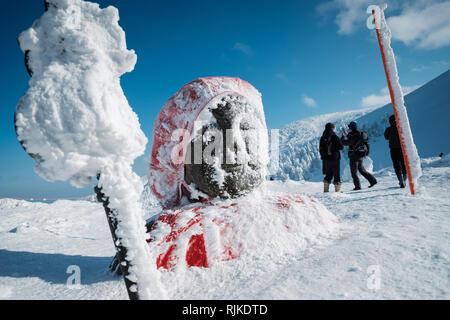 """Eine Jizo ist an der Spitze der Schnee monster Bäume, am 5. Februar 2019 angezeigt. Ursache eine warme Winter die Saison für seltsam geformte, schneebedeckte Bäume, nicknamed jetzt Monster"""" vorbei ist. 'Monsters' in der Regel den Hängen des Mount Zao in Japan. Mount Zao, einer 1.841 hohen Vulkan gebietsübergreifende Yamagata und Miyagi Präfekturen, ist einer der wenigen Orte in Japan, wo das Phänomen der jetzt Monster"""" gesehen werden kann. Starke Winde über den nahe gelegenen See schleudern Wassertröpfchen, die Freeze gegen die Bäume und ihre Äste bis in der Nähe von - horizontale Eiszapfen fangen an sich zu bilden. Fallenden Schnee auf dem Eis formatio - Stockfoto"""
