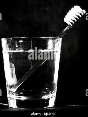 Gebrochen Bild eines Handstück wie in ein Wasserglas Wasser gesehen - Stockfoto