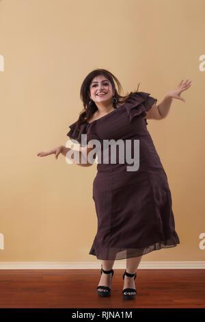 Fette Frau in einem langen braunen Kleid tanzen auf High