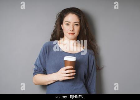 Entspannt junge Frau auf ihre Kaffeepause - Kaffee in das verfügbare Papier Schale zu gehen, lehnte sich gegen graue Wand - Stockfoto