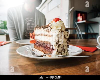 Deutsche Frau, die köstliche Erdbeere Schwarzwald Dessert mit Tasse Kaffee in der Cafeteria - Stockfoto