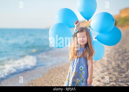 Nettes Mädchen mit Ballons am Strand von Ozean Meer Küste mit Sandstrand felsige Land posiert, ein Urlaub, ein Meer Reise. - Stockfoto