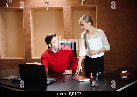 Zuversichtlich Boss mit Papier erklärt etwas zu Sekretär in t - Stockfoto