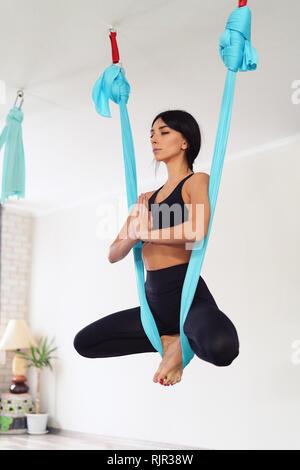 Volle Länge des passen junge Frau tun antigravity Yoga Übungen im Studio. Namaste Schmetterling darstellen. Seitenansicht - Stockfoto