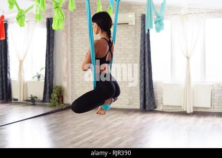 Volle Länge des passen junge Frau tun antigravity Yoga Übungen im Studio. Namaste Schmetterling darstellen. Seite zurück. - Stockfoto