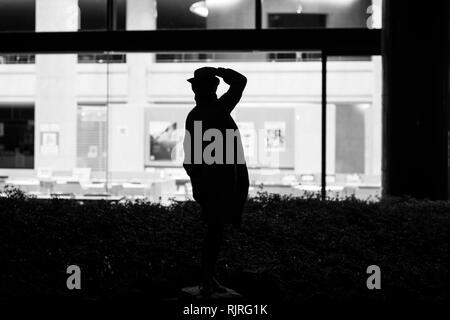 Statue des Menschen scheinbar auf der Suche nach verlassenen Open Office Space in der Nacht - Stockfoto