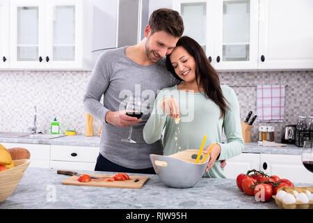 Lächelnde Frau Besprühen die Butter, die mit ihrem Mann in der Küche Holding Wein Glas - Stockfoto