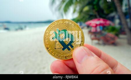 Hand mit goldenen bitcoin am Strand, auf dem Hintergrund der sea wave. Bitcoin ist eine moderne Art der Austausch dieser crypto Währung ist ein bequemer bedeuten - Stockfoto