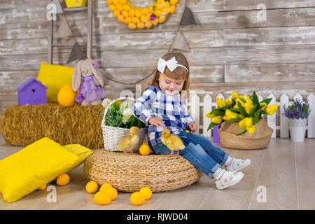Süße kleine Mädchen mit rustikalen Jeans mit Versteck spielen und mit einem Huhn auf einem Heuhaufen sitzen suchen. Das Konzept der Kinder mit Tieren. Studio. - Stockfoto