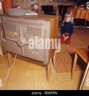 Fernsehen in den 1960er Jahren. Ein Mädchen sitzt vor einem Fernseher mit ihren Augen auf dem Bildschirm und das Programm gesetzt. Schweden 1969 - Stockfoto