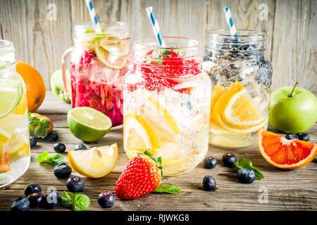 Auswahl verschiedener Obst und Beeren Limonade Getränke, Imbiss infundiert Wasser, in Mason Gläser, mit frischen Erdbeere, Zitrone, Limone, Orange, Heidelbeere, w - Stockfoto