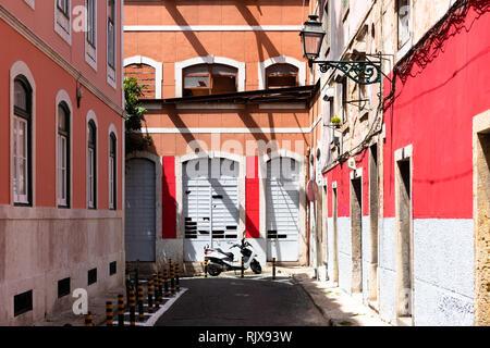 Kleine Gasse mit roten und weißen Wänden und Scooter. - Stockfoto