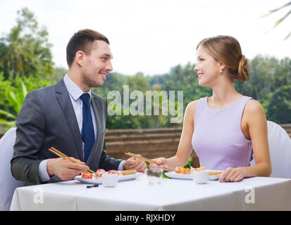 Lächelndes Paar essen Sushi Rollen im Restaurant - Stockfoto