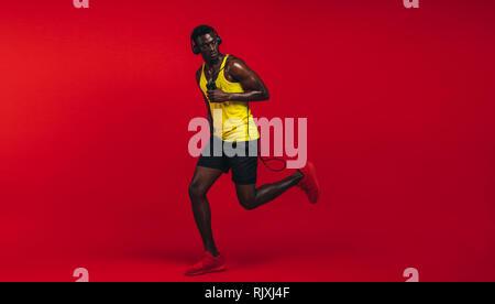 Volle Länge des gesunden jungen afrikanischen Mann laufen mit dem springen Seil über den roten Hintergrund. Afrikanische fitness Modell in Sportbekleidung im Studio. - Stockfoto