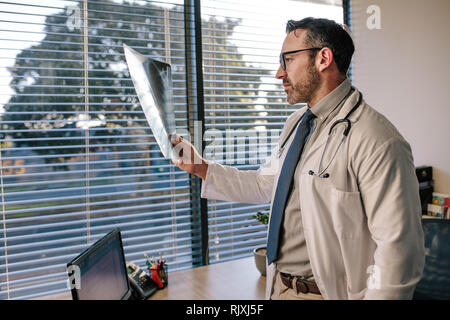 Reife männliche Arzt auf eine Radiographie. Arzt schaut auf einen x-ray von seinem Patienten in seinem Büro. - Stockfoto