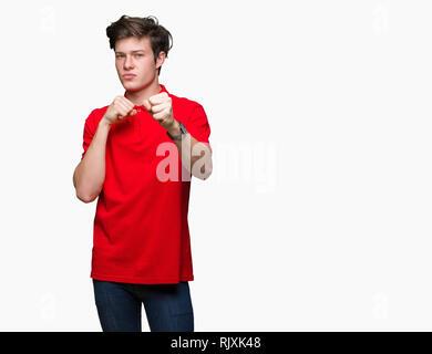Jungen gutaussehenden Mann tragen rote T-Shirt über isolierte Hintergrund Stanzen Faust zu kämpfen, aggressiv und wütend Angriff, Bedrohung und Gewalt - Stockfoto