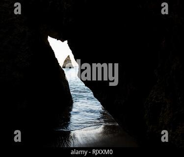 Auf der Suche durch die Öffnung in der Felswand an der Spitze Felsformation in der Entfernung, Alvor, Algarve, Portugal, Europa - Stockfoto