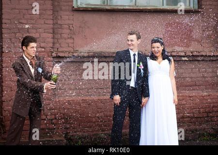 Ein Zeuge bei der Hochzeit geöffnet Champagner mit Farbakzenten