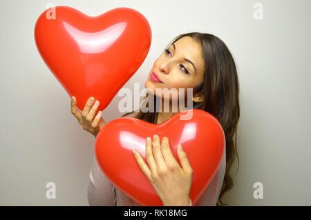Valentinstag Konzept. Schöne Mädchen küssen herzförmige Ballons und andere in ihren Arm auf grauem Hintergrund. - Stockfoto