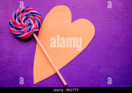 Candy Swirl rainbow Runde zwei Lutscher auf Herzförmigen. Candy Stripes auf einem Stock auf blauem Hintergrund. Liebe Konzept. Februar 14. Urlaub glücklich Valent - Stockfoto