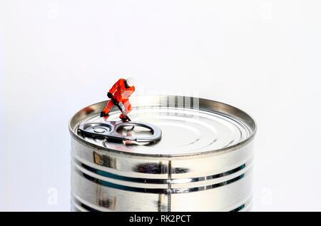 Konzeptionelle diorama Bild von Miniatur Abbildung Arbeiter versuchen, eine Dose zu öffnen, - Stockfoto