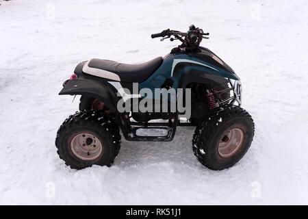 Close-up ATV Allrad Quad Bike im Wald im Winter. 4WD-Fahrzeug terreain stand bei starkem Schneefall mit tiefen Spur. Saisonale extreme Sport Abenteuer eine - Stockfoto